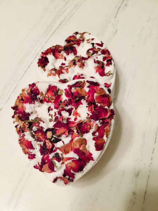 Heart shaped white bath bomb embedded with rose petals