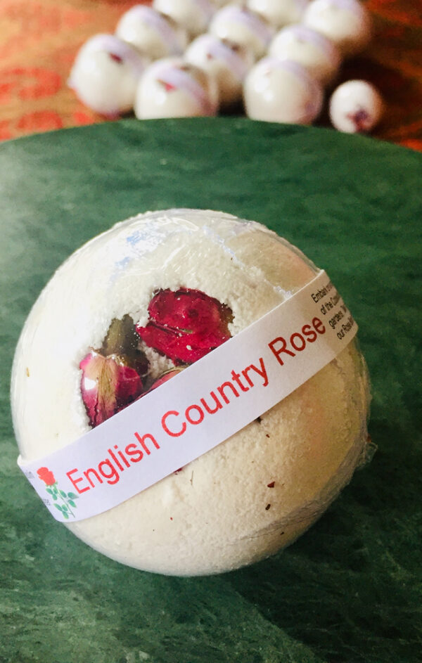 Beautiful white bath bomb encrusted with miniature rosebuds sitting on the edge of an inviting bath