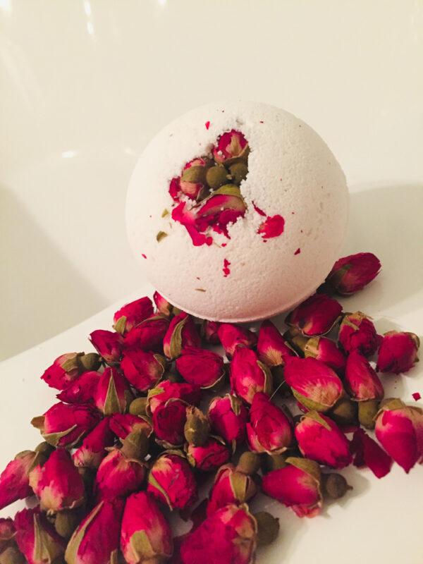 Beautiful natural white bath bomb embedded with miniature red rosebuds sitting in a spill of rosebuds on the edge of an inviting bath