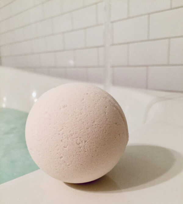 all natural off white bath bomb sitting waiting for you on the ledge of a beautiful bath