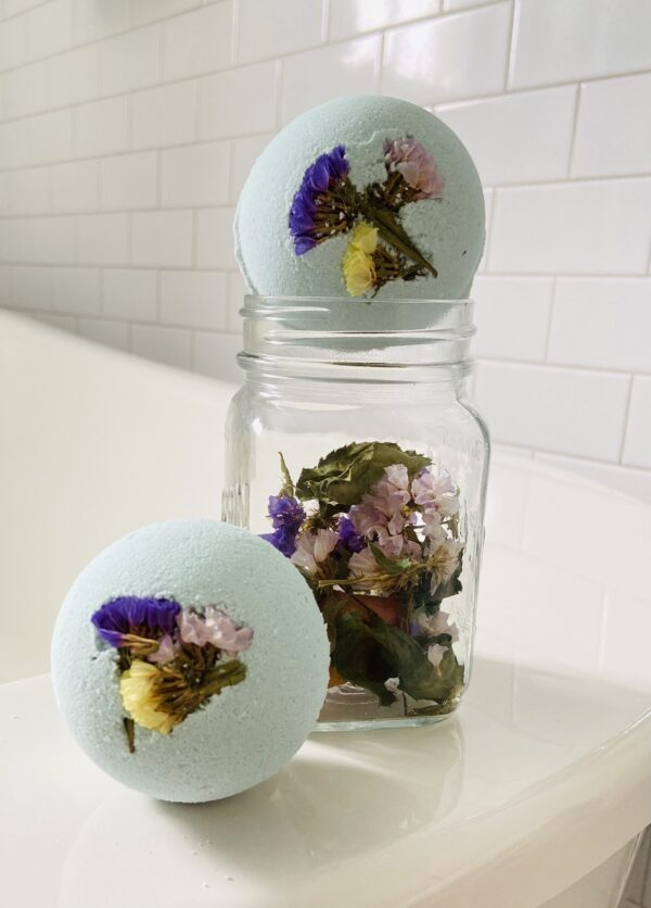 A pretty and delicate light blue bath bomb embedded with a tiny bouquet of violet, mauve and yellow dried flowers