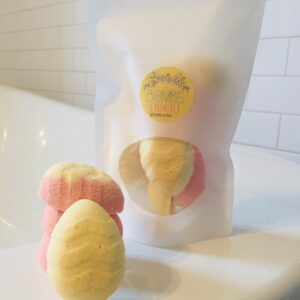 Pastel yellow and pink Easter egg shaped mini bath bombs beside a white package on a white bath tub against a lovely white tiled background