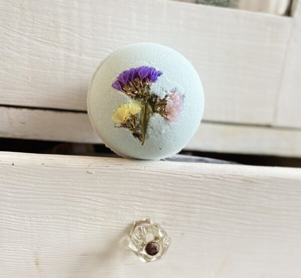 A pretty and delicate light blue bath bomb embedded with a tiny bouquet of purple, mauve and yellow dried flowers