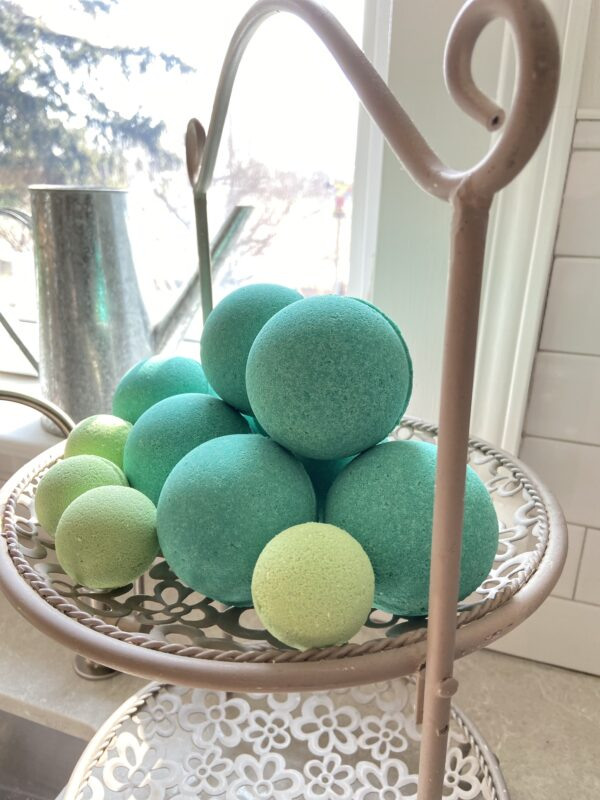 Bright kelly green bath bomb and lime green mini bath bombs clustered on a vintage pie rack against a white tiled background with window and metal watering can behind display.