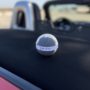 Black and white bath bomb sitting on the back of a red convertible sports car with the beach and blue sky in the background