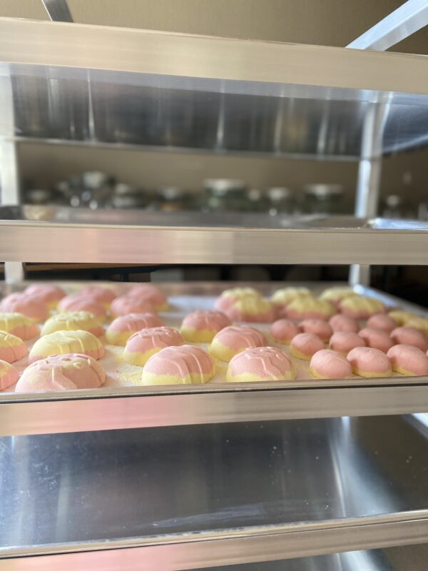 Pastel pink and yellow egg-shaped bath bombs drying on a silver tray