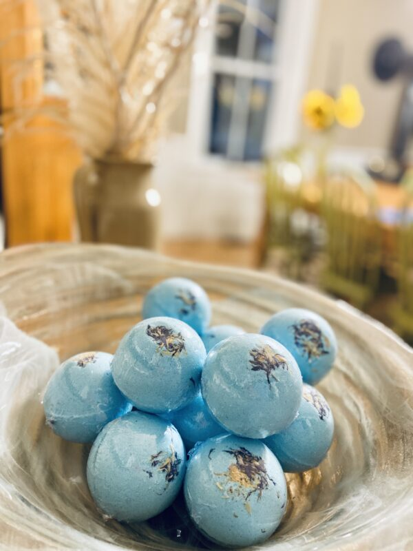 Blue bath bombs with purple corn flower and yellow chysanthumum petals stacked in a glass bowl