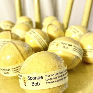 Bright yellow mini bath bombs wrapped with a yellow band with a SpongeBob picture and grouped on a yellow chair.